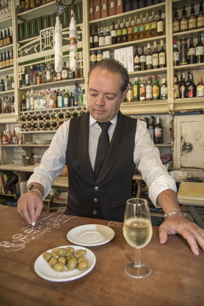 Spanien, Andalusien, Provinz Sevilla, Sevilla, Tapas Bar E Rinconcillo: eine der ältesten Tapa Bars in Sevilla. KellnerJose Carbajo notiert die rechnung auf dem Tresen