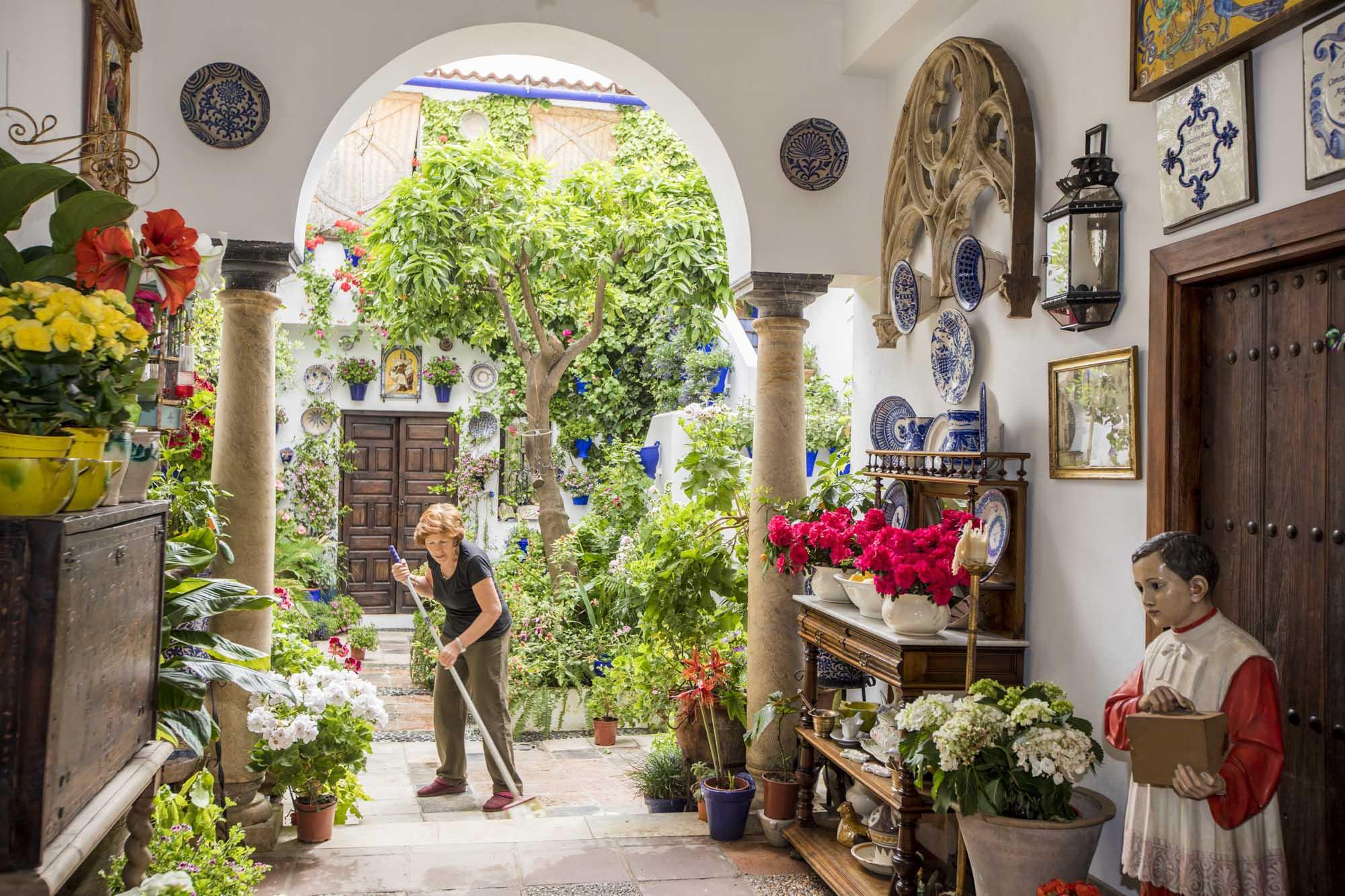 Spanien, Andalusien, Cordoba, Patio, Calle Pastora 2, Candida, die Mutter von Rafael Barón, putzt den Patio für das Festival. Der Patio ist der meißt prämierte in der Sektion moderne Architektur. Rafael ist Präsident der Patio-Vereinigung Asociación Claveles y Gitanillas.