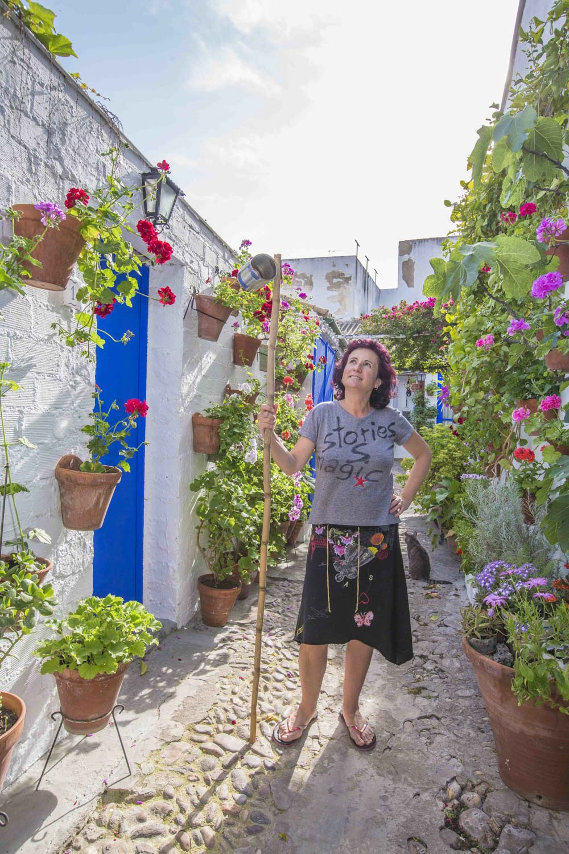 Spanien, Andalusien, Cordoba, Patio, Calle Marroquies 6. Maria Angeles Arquero hat eine Werkstatt für Kosmetik Produkte in dem Patio, den Stab mit Konservenbüchse braucht sie zum Blumengiessen. Der Patio ist ein Mini-Viertel mit sieben verwinkelten Gassen. Hier lebten einst bis zu 23 Familien mit einem Gemeinschaftsbad und Gemeinschaftsküche. Der Patio wurde in den vergangen 30 Jahren viel prämiert.