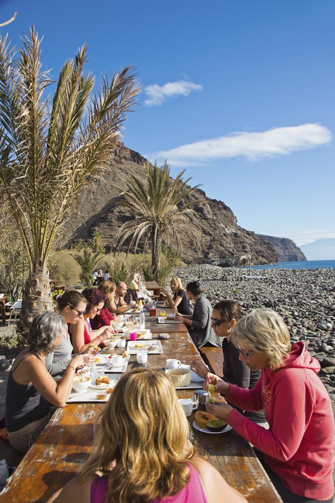Spanien, Kanarische Inseln, La Gomera, Landhotel & Biohof Hotel El Cabrito, Terrasse, Yoga Teilnehmer, Frühstück unter Palmen.