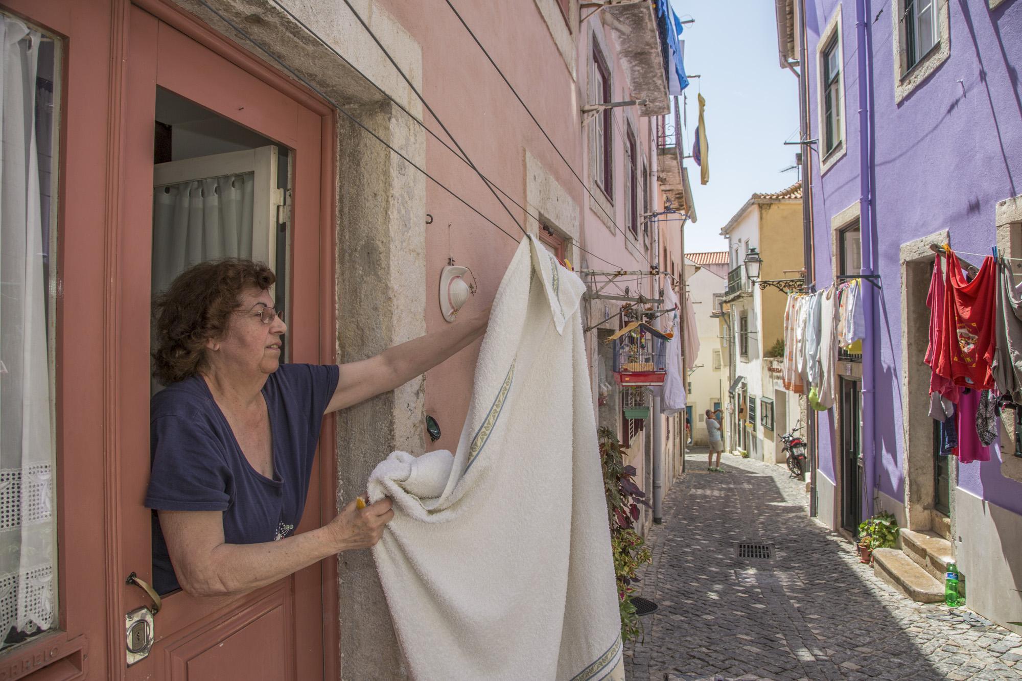Portugal, Lissabon, Alfama Viertel, Rua das Flores de Santa Cruz, Gasse, Anwohnerin Gabriela LAmbim hängt Wäsche vor der Tür auf