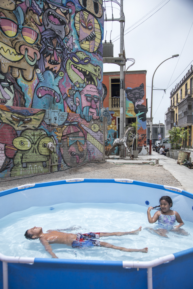 Peru, Lima, Callao Viertel, Monumental Callao, Kinder baden im Pastik Pool, Künstler Viertel, Graffiti, Strassen Szene, Street Art, Wandmalerei, schwimmen, Sommer, Wasser  Engl.: Peru, Lima, Callao district, Monumental Callao, children bathe in the pastic pool, artist district, graffiti, street scene, street art, wall painting, swimming, summer, water