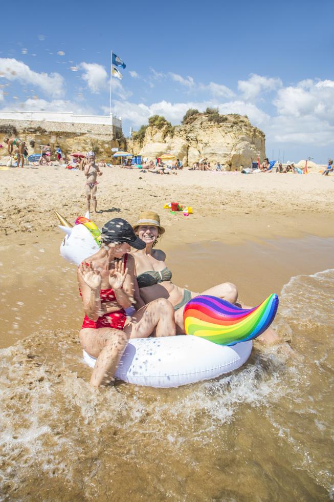 Portugal, Algarve, Atlantikküste, Lagos, Stadtstrand; Praia Batata. Touristen Dasha und Lena am Strand mit aufblasbarem Einhorn.
