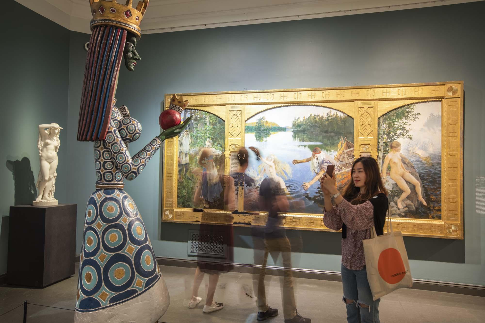 Finnland, Helsinki, Kunstmuseum Atheneum, Bilder von grossen, finnischen Meistern. Besucher vor dem Aino Triptychon von Akseli Gallen-Kallela