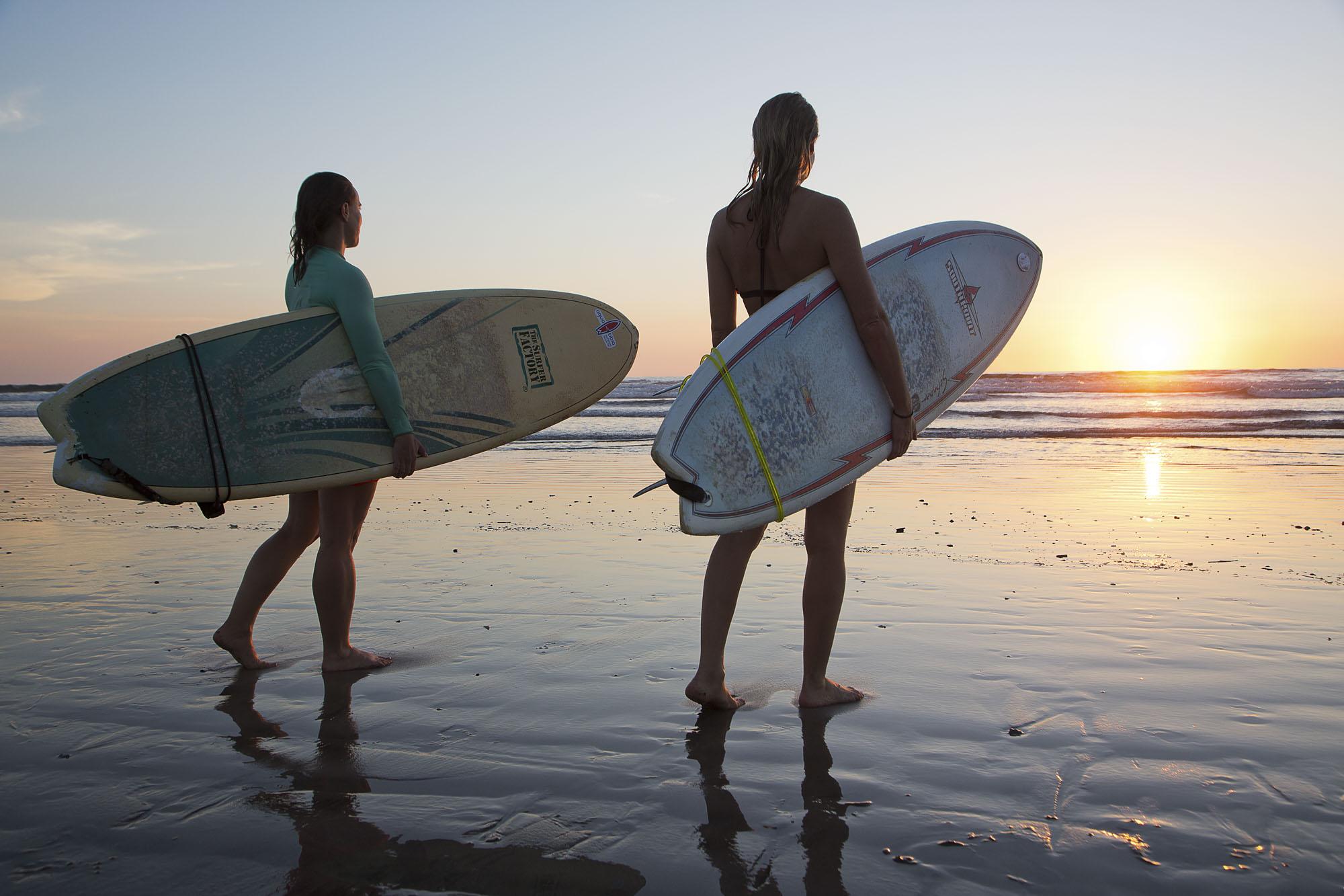 Costa Rica, Provinz Guanacaste, Nosara, Playa Guiones, zwei Mädchen mit Surfboards , Sonnenuntergang